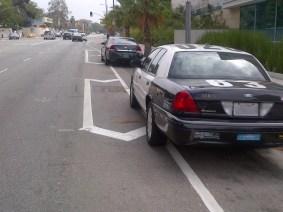 Police car parked on bike lane.