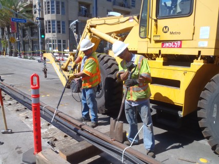 Workers conducting a holiday test - a high voltage electrical test which is performed to test the rail boot for any punctures or any gaps in the boot.