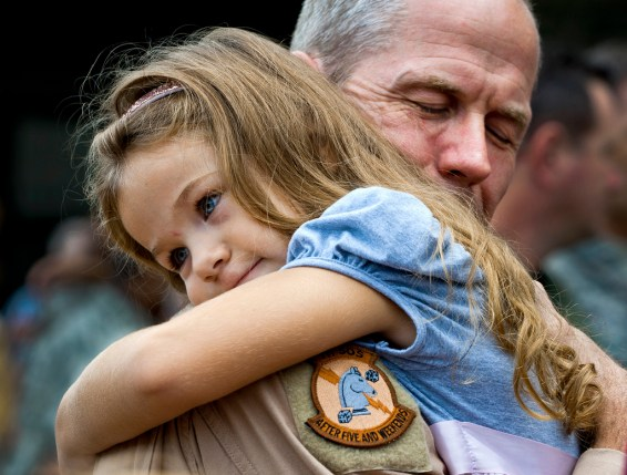 U.S. Air Force Lt. Col. Thomas Frazier of the 711th Special Operations Squadron receives an overdue hug from his daughter after returning from a deployment to Southwest Asia, Aug. 7, 2011. More than 25 Air Force Reserve Airmen were welcomed back home at a homecoming party at Duke Field, Fla. (U.S. Air Force photo by Tech. Sgt. Samuel King Jr.)