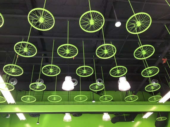 The facility is painted in bright apple green. The ceiling features a collection of green bicycle rims similar to the film reel design found at Hollywood/Vine Metro Red Line Station.