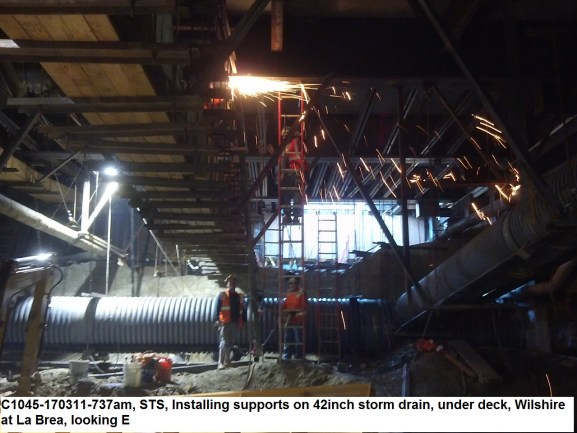 C1045-170311-737am, STS, Installing supports on 42inch storm drain, under deck, Wilshire at La Brea, looking E
