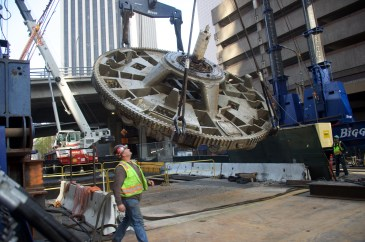 The tunnel boring machine cutterhead is extracted from below ground with a gantry crane. Photo by Gary Leonard.