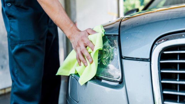 A man wiping away water on a headlight.