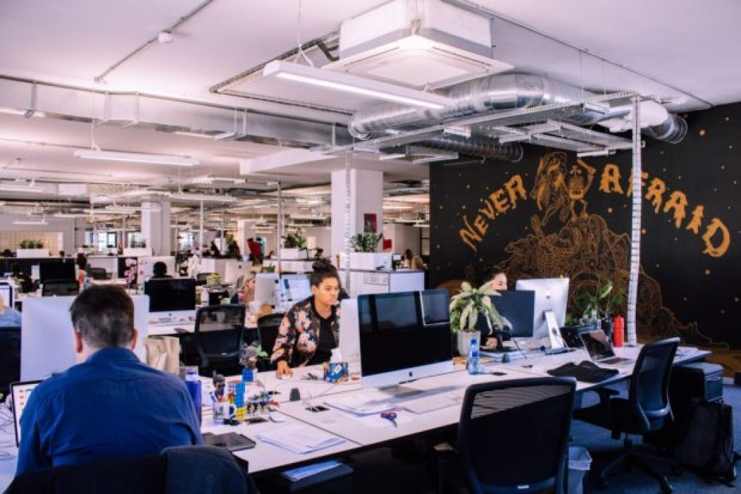 """a creative office in cape town with staff sitting at their desks working on macs, on the right is a black wall with """"never afraid"""" written on it"""