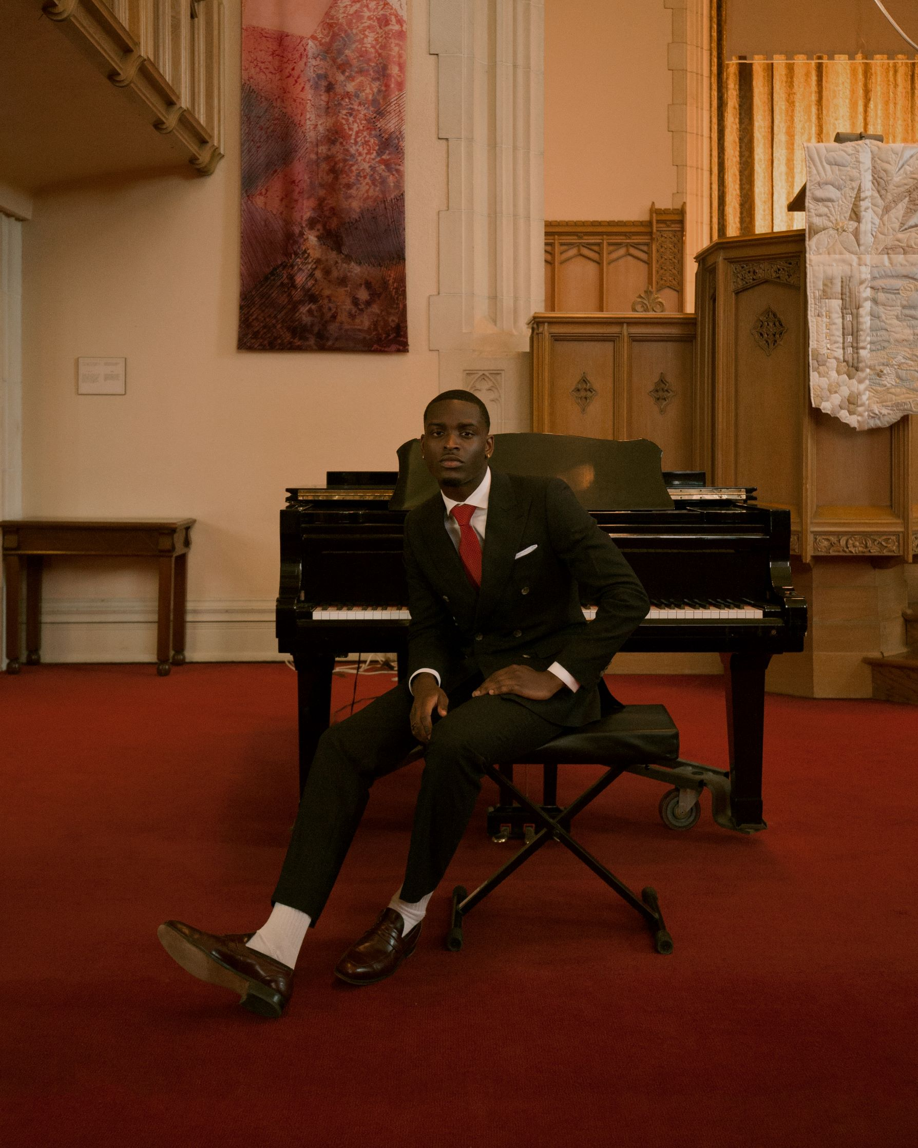 Josef Adamu in a Black suit in front of a piano in a church