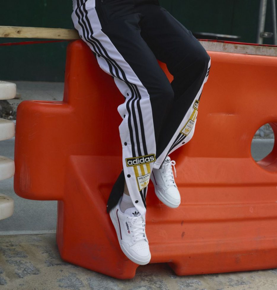 Adidas track pants and Adidas Continental sneakers being worn by a person sitting on an orange barrier