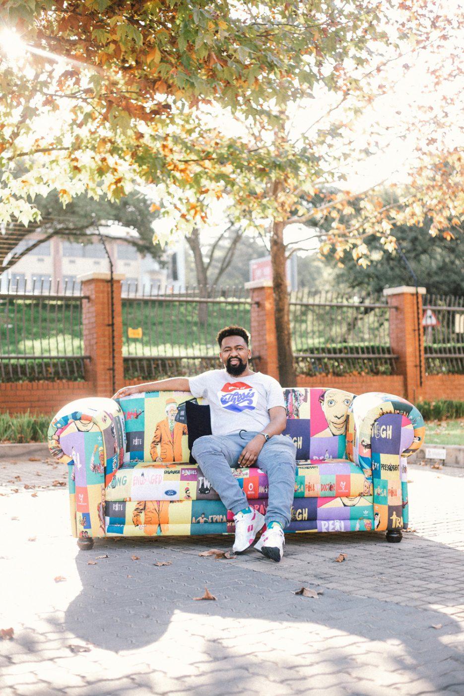 Graphic designer and illustrator David Tshabalala on a couch he designed. Image by Khotso Tsagaane.