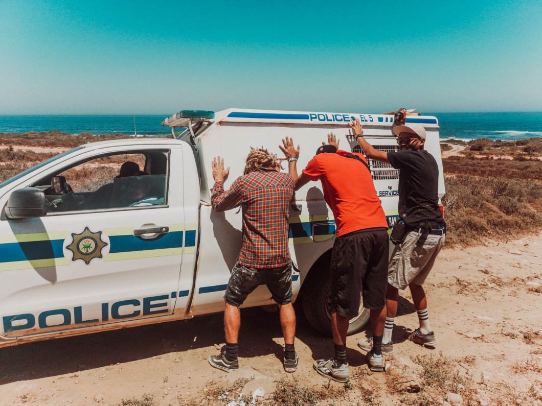 Graffiti artists jokingly pushing a police vehicle