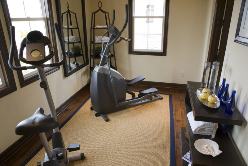 Small nicely designed home gym with wood floor and large exercise mat with elliptical trainers and side table with refreshments and towels