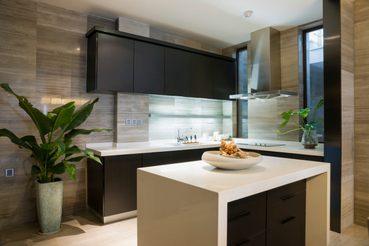 Elegant modern kitchen with simple white island, multi-colored wall and black cabinets