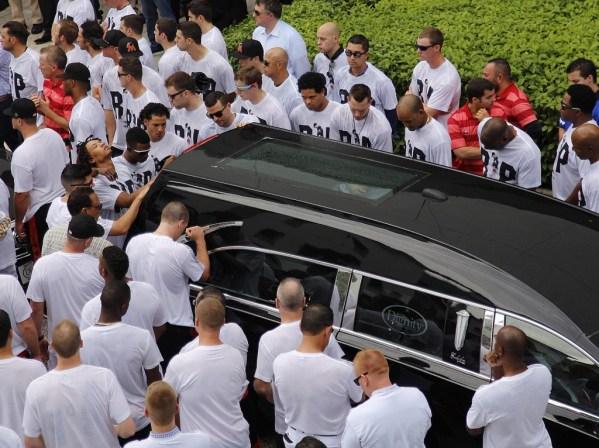 Jugadores de los Miami Marlins caminan al costado del coche fúnebre mientras sale del Estadio (AP)