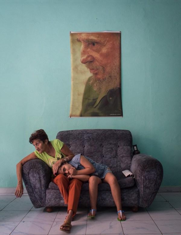 Gente, tercer premio. Una mujer acaricia la cabeza de una niña en un sofá en una estación de policía enCamaguey, Cuba. Kristina Kormilitsyna, Kommersan