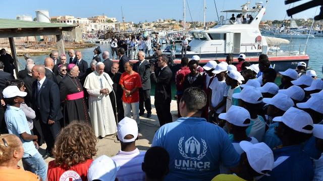 8 de julio de 2013, Lampedusa, Italia: el papa Francisco se encuentra con un grupo de inmigrantes en su primer viaje fuera de Roma. Poco después subió a un bote de pescadores para rendir homenaje en el mar a quienes perdieron la vida tratando de llegar a Europa por esa vía (Tullio M. Puglia/Getty Images)