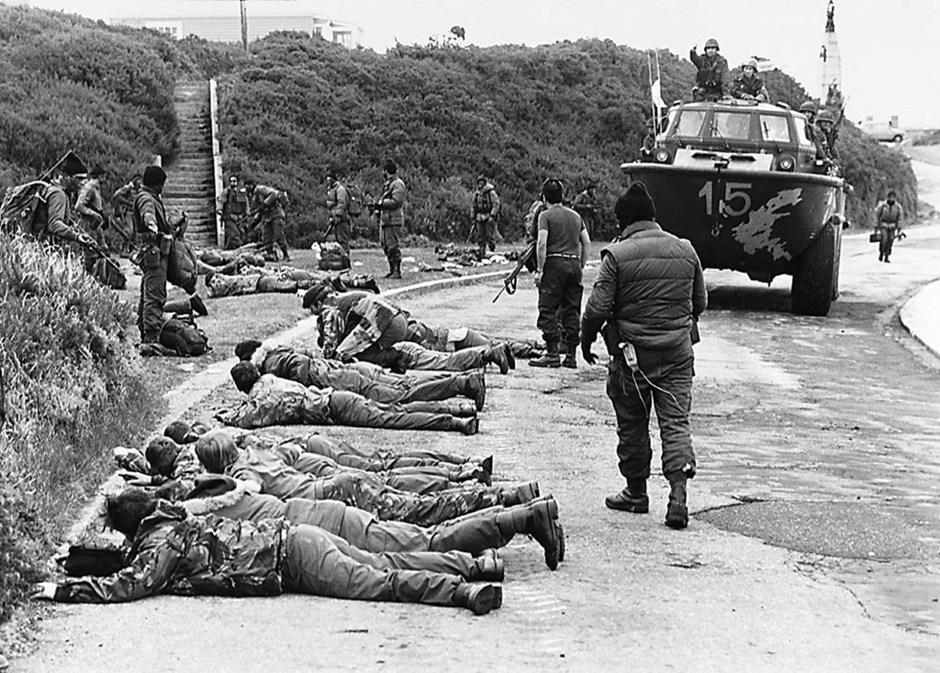En Ross Road, Puerto Argentino, los marines deponen sus armas frente a los comandos anfibios de la Armada Argentina. En los enfrentamientos cae el Capitán Pedro Edgardo Giacchino y resultan heridos de gravedad el Teniente de Fragata Diego García Quiroga y el Cabo Primero Ernesto Urbina (Rafael Wollman)