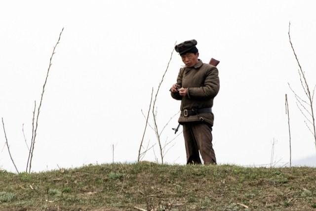Un soldado prepara un cigarrillo cerca al río Yalu. A pesar de que el domingo el régimen comunista llevó a cabo un lanzamiento de misil fallido, los soldados que se ven desde los barcos chinos parecen muy tranquilos