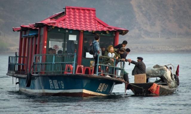 Un hombre vende productos norcoreanos a los turistas chinos que llegan en pequeños cruceros turísticos, en el río Yalu. Los barcos se acercan hasta tan sólo unos metros de la costa coreana, lo que permite a los turistas ver el país sancionado internacionalmente por su programa nuclear