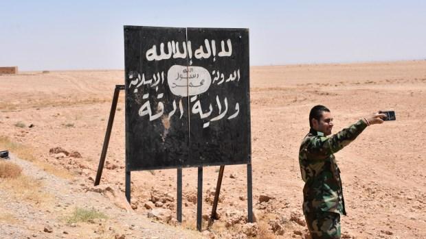 Un soldado frente a un cartel de propaganda del Estado Islámico (AFP)