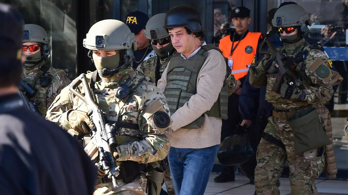 Víctor Manzanares es trasladado y camina custodiado, con casco y chaleco antibalas (Télam)