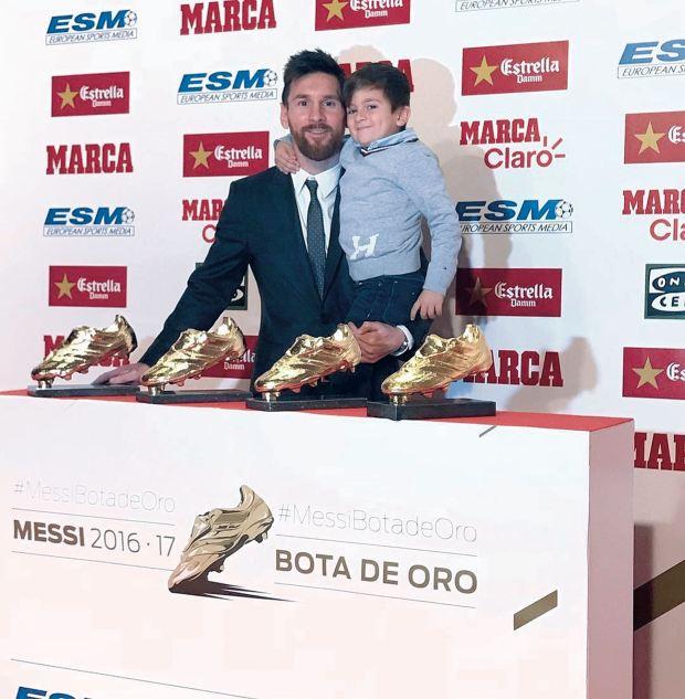 Thiago con papá y sus botines de oro. Foto: AFP
