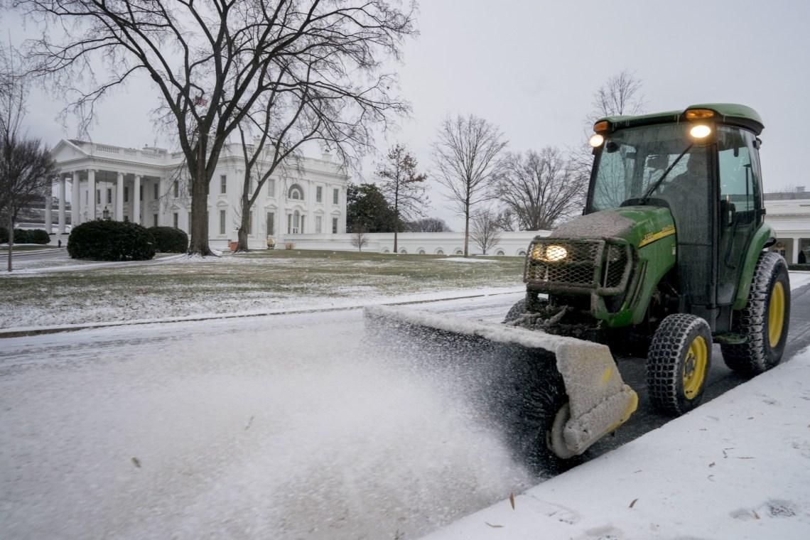 La Casa Blanca también amaneció con una capa de nieve. Un trabajador del Servicio Nacional de Parques limpia los jardines (AP)