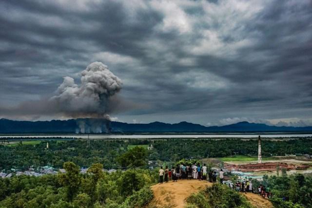 Watch Houses Burn – Mirar casas quemar: un grupo de rohingyas en el asentamiento de Leda en Cox's Bazar, Bangladesh, observan cómo las casas se incendian justo al otro lado de la frontera en Myanmar. (Masfiqur Sohan, Bangladesh)