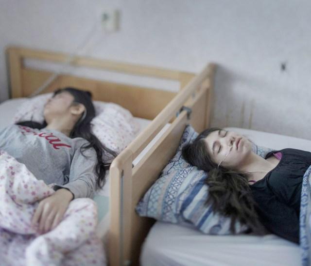 Resignation Syndrome – Síndrome de renuncia: Djeneta (derecha) lleva dos años y medio postrada en cama e insensible, y su hermana Ibadeta desde hace más de seis meses, con síndrome de renuncia, en Horndal (Suecia). Es una condición que se cree que sólo existe entre los refugiados en Suecia. (Magnus Wennman, Suecia)