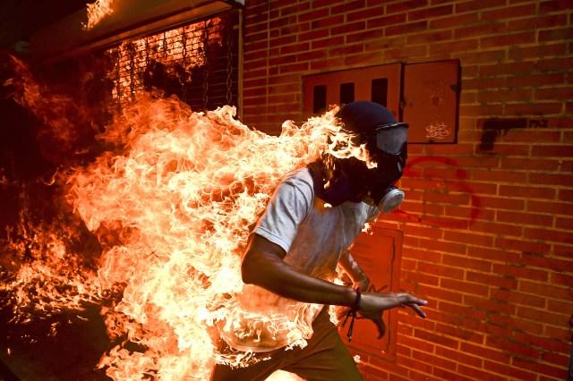 Venezuela Crisis – La crisis de Venezuela: foto nominada para la Foto del Año y para la categoría Noticias En Vivo-Sencillos en el concurso de fotografía World Press. José Víctor Salazar Balza (28) se incendia en medio de violentos enfrentamientos con la policía durante una protesta contra el presidente Nicolás Maduro en Caracas, Venezuela. (Ronaldo Schemidt, Venezuela)