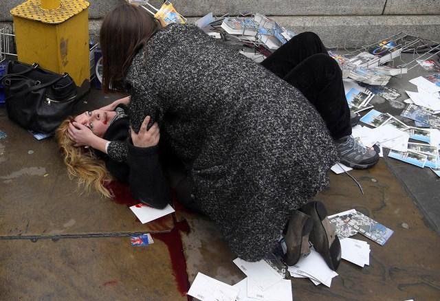 Witnessing the Immediate Aftermath of an Attack in the Heart of London – Atestiguando la Inmediata Posterioridad de un Ataque en el Corazón de Londres: foto nominada para la Foto del Año y para la categoría Noticias En Vivo-Historias en el concurso de fotografía World Press. Un transeúnte reconforta a una mujer herida después de que Khalid Masood condujera su auto contra peatones en el puente de Westminster en Londres, Reino Unido, matando a cinco personas e hiriendo a muchas otras. (Toby Melville, Reino Unido)