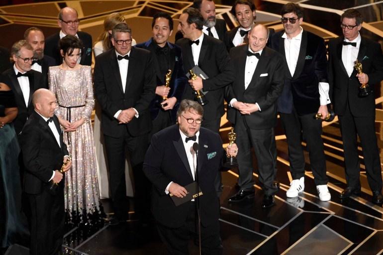 """Guillermo del Toro y su equipo con todas las estatuillas que ganaron por """"La forma del agua"""" en los Oscar 2018– Fotos: Invision/AP – Reuters – Getty Images/AFP"""
