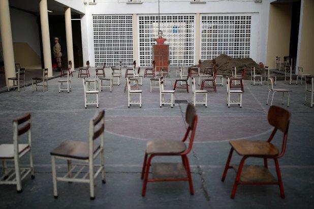Un miembro de la milicia monta guardia ante las sillas donde se hace la fila, vacías ante la falta de votantes en Caracas (Reuters)