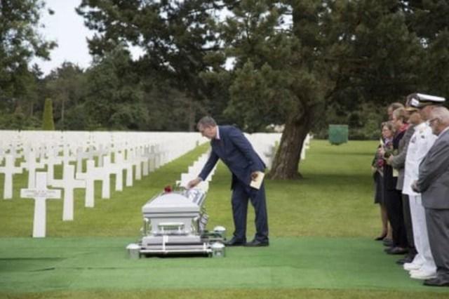 Louis Pieper, un sobrino de los gemelos, coloca una rosa encima de la tumba de Normandía. (Cortesía de American Battle Monuments Commission.)
