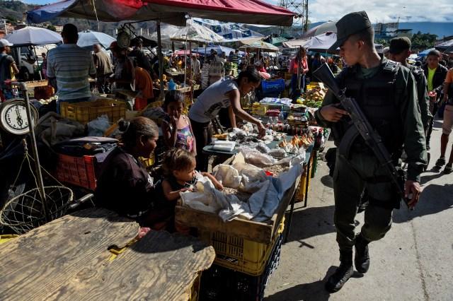 Un miembro de la Guardia Nacional bolivariana en el mercado de Coche, un barrio de Caracas, para inspeccionar los precios (AFP/ Federico PARRA)