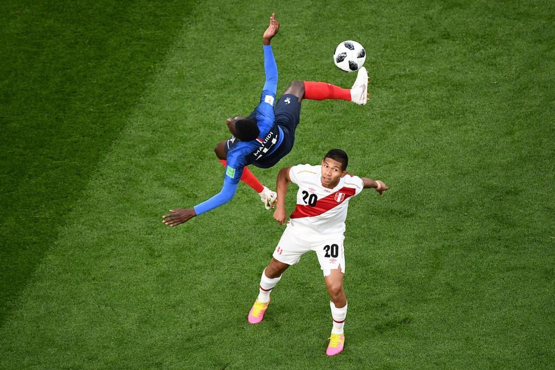 El francés Blaise Matuidi vuela por el aire al ir en busca de la pelota con el peruano Edison Flores