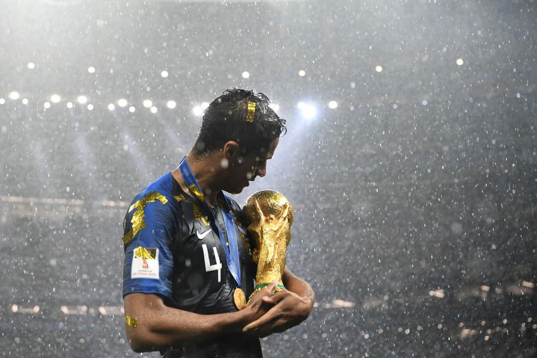 El francés Raphael Varane sostiene a la Copa del Mundo como si fuera un bebé