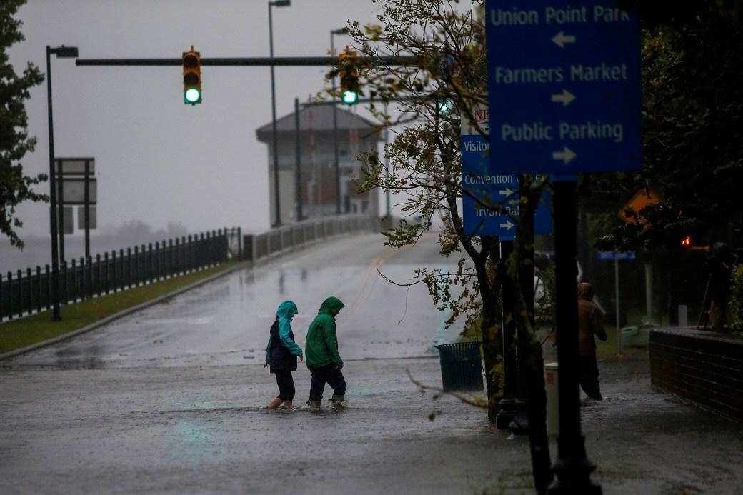 Dos personas cruzan una avenida abajo de una lluvia torrencial.