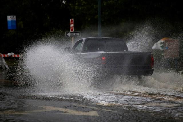 Una camioneta atraviesa sobre las calles llenas de agua.