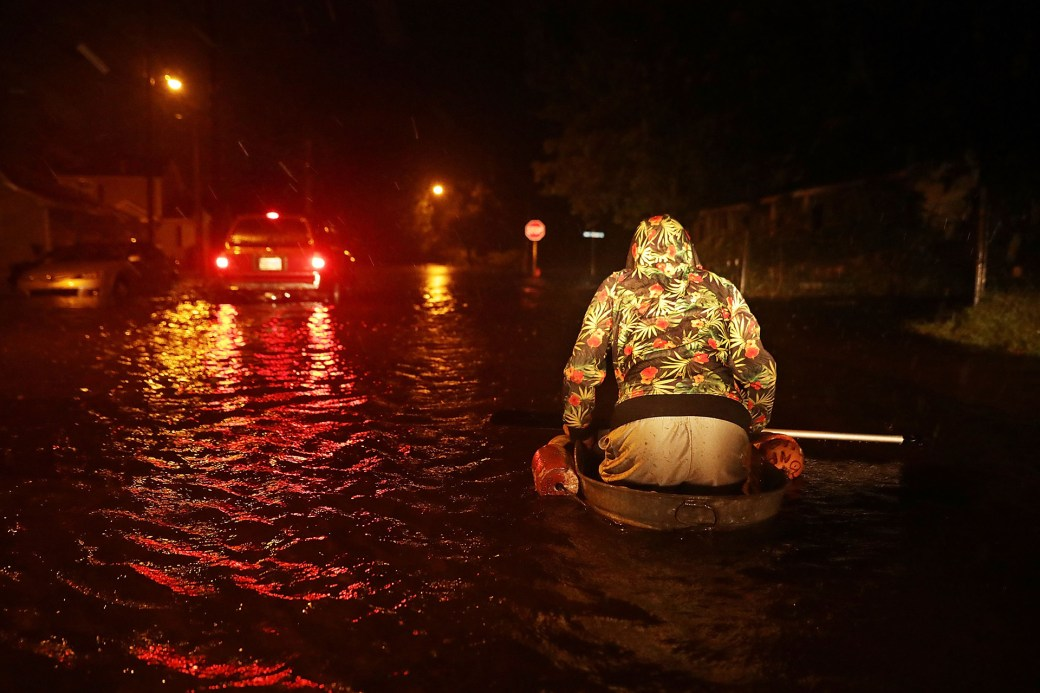 Un hombre llamado Michael Nelson navega en un bote improvisado hecho de una bañera de metal y flotadores de pesca después de que el río Neuse inundara su calle durante el huracán Florence.