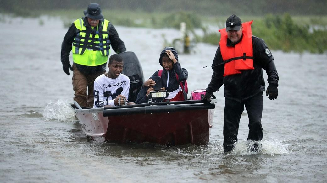 Dos socorristas se llevan a una familia en una pequeña embarcación