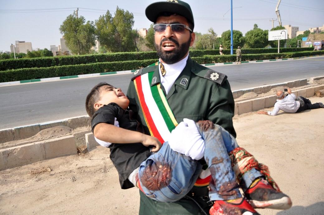 Un miembro de la Guardia Revolucionaria iraní cargando a un niño herido(AP)