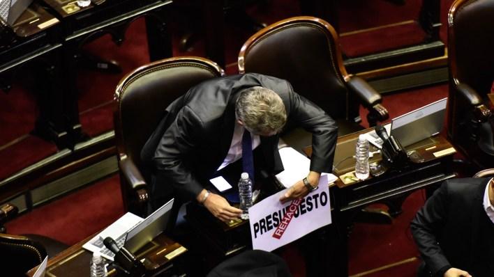 Agustín Rossi coloca un cartel en su banca (Fotos: Adrián Escandar)