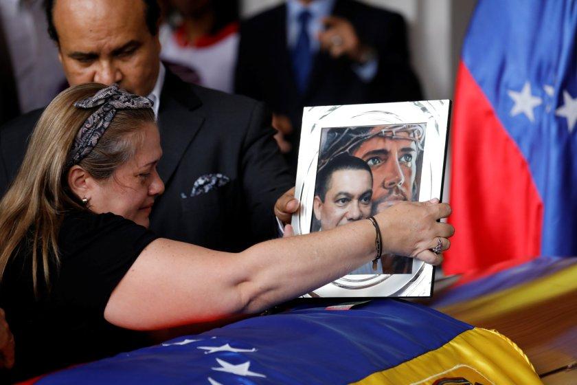 Luz Alban pone una foto sobre el ataúd de su hermano Fernando Alban durante una ceremonia en la Asamblea Nacional de Caracas (REUTERS/Marco Bello)
