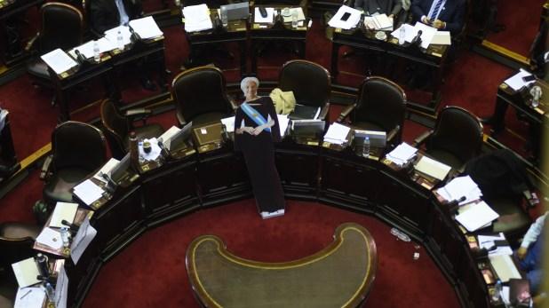 La falsa Christine Lagarde, con la banda presidencial, en el medio del recinto