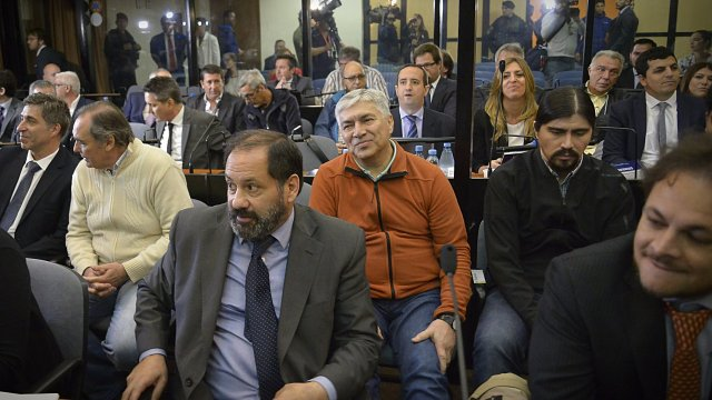 Báez, de pulover naranja en la primera audiencia del juicio. A su izquierda su hijo Martín y a la derecha el contador Pérez Gadín (Gustavo Gavotti)