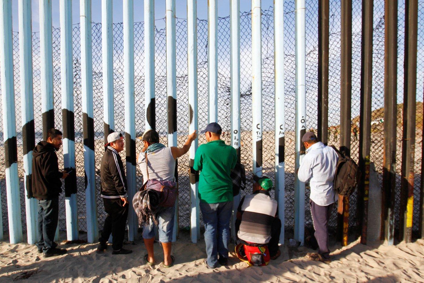 Miembros de la caravana migrante que intenta llegar a EEUU observan a través del vallado fronterizo en Tijuana, Mexico (REUTERS/Jorge Duenes)