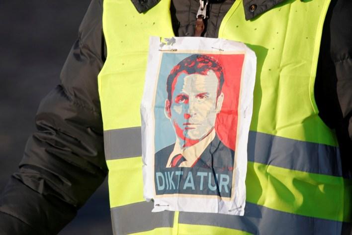 """Un manifestante de chalecos amarillos con la cara del presidente Macron y la palabra """"dictador""""(REUTERS/Charles Platiau)"""