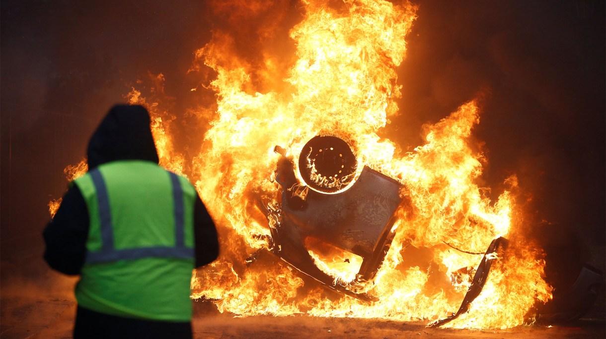 Un manifestante con su chaleco amarillo, delante de un automóvil incendiado y volcado en París(Reuters)