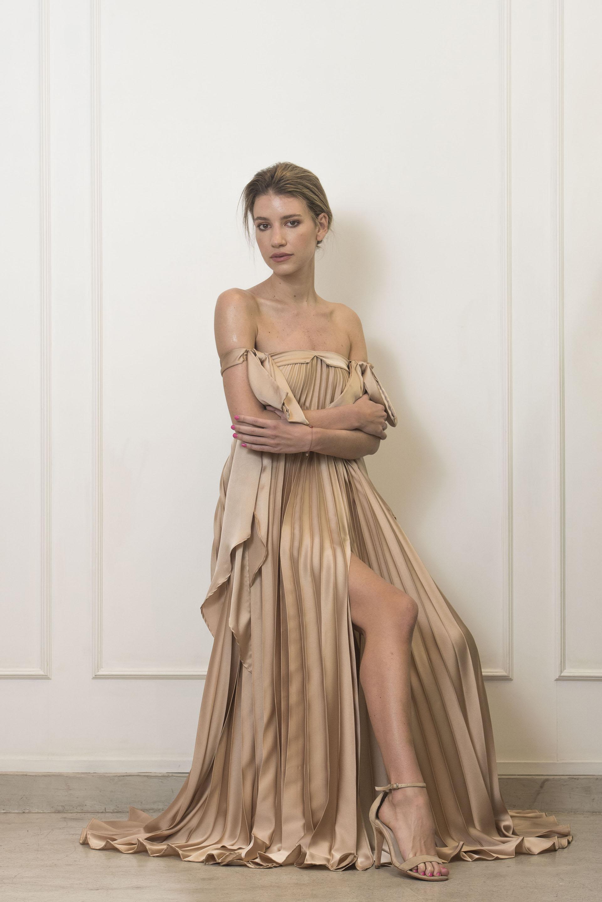 Un vestido plisado con escote barco coronado por un moño en cada brazo. El tono es el gran protagonista: seda en oro