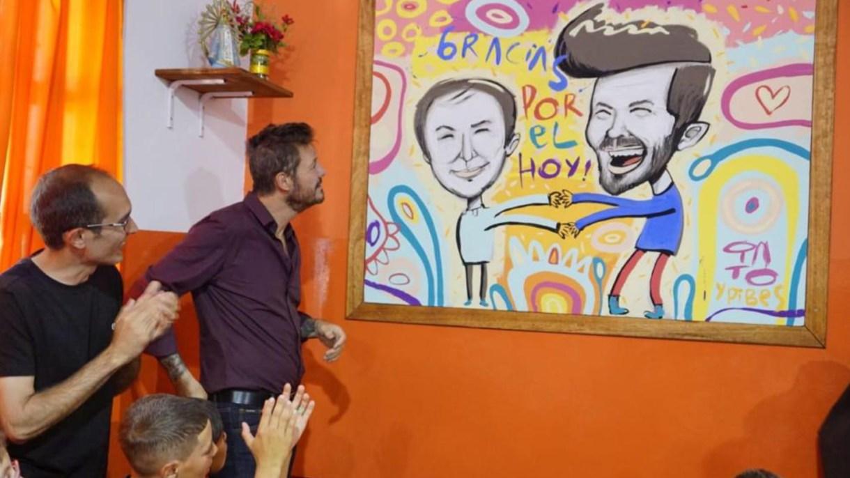 Junto al intendente, Marcos Pisano, Tinelli observa una caricatura suya y del párroco