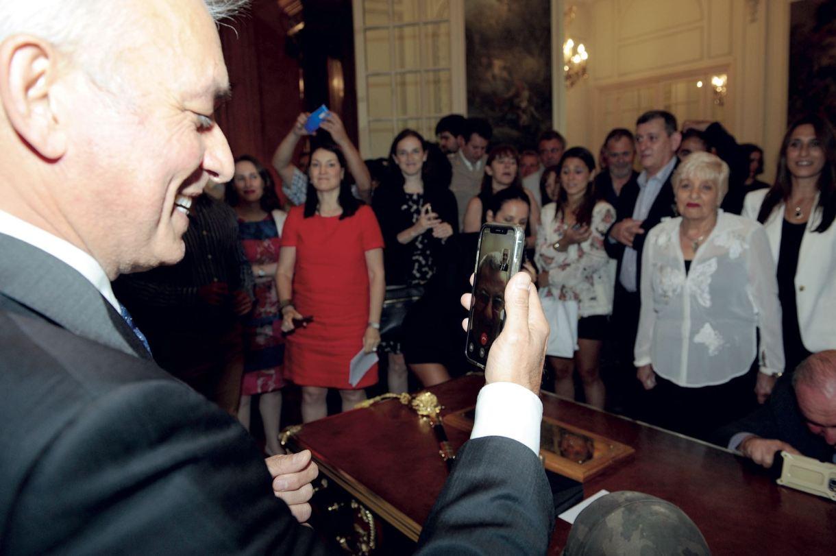 Gorzelany en pleno acto en el Palacio San Martín, rodeado por su familia y funcionarios, en comunicación vía celular con Goodal.