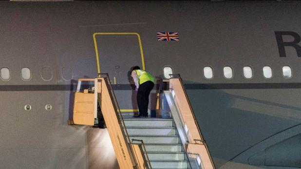 Un empleado del aeropuerto de Ezeiza espía por la mirilla del avión a la espera del descenso de la Primera Ministra de Reino Unido, Theresa May, para la reunión de G20 (Julieta Ferrario)